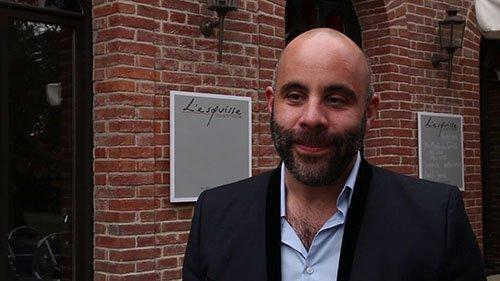 Portrait d'un homme devant une facade d'un restaurant